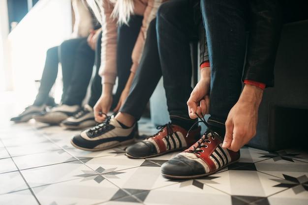ボウリング場のプレーヤーは、家の靴に靴ひもを結びます。
