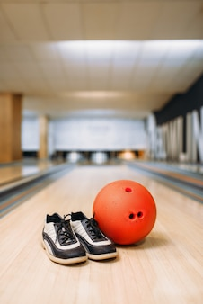 Bowling ball and house shoes on lane in club, pins, nobody. bowl game concept, tenpin