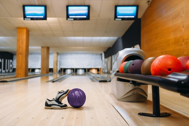 Bowling ball and house shoes on wooden floor in club, pins, nobody. bowl game concept, tenpin