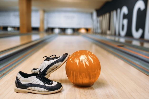 Bowling ball and house shoes on wooden floor