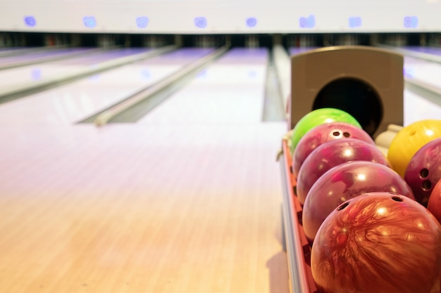 Bowling balls on a stack with the bowling alley background