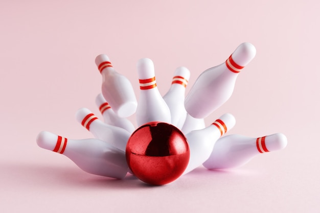 Bowling strike hit on pastel pink background.