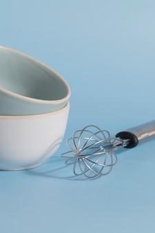 青い背景の台所用品のボウルと泡立て器