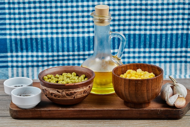 Bowls of boiled sweet corn and green peas, spices, oil, and vegetables on a wooden board with a tablecloth.