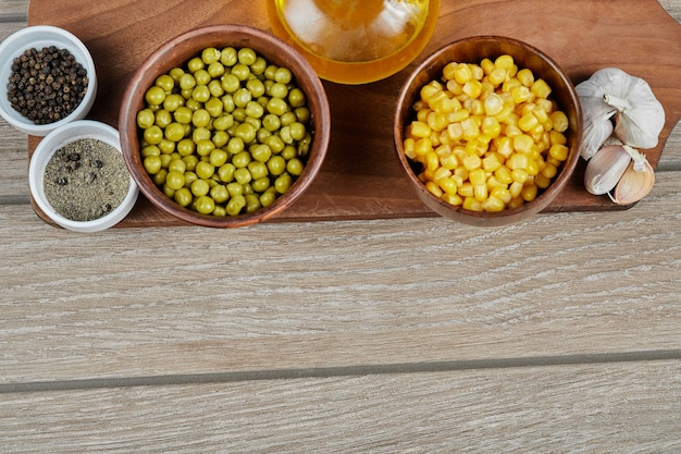 Bowls of boiled sweet corn and green peas, spices, oil, and vegetables on a wooden board.