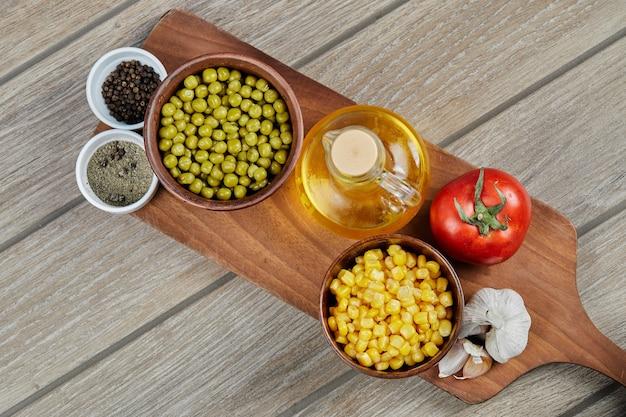 Ciotole di mais dolce bollito e piselli, spezie, olio e verdure su una tavola di legno.
