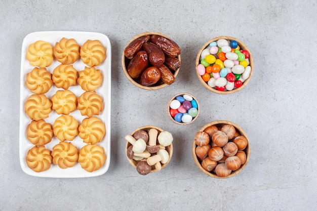 Bowls of candies, hazelnuts, dates and chocolate mushrooms next to cookies on a plate on marble background. high quality photo