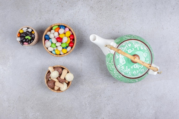 Bowls of candies and mushroom chocolate next to ornate teapot on marble background. high quality photo