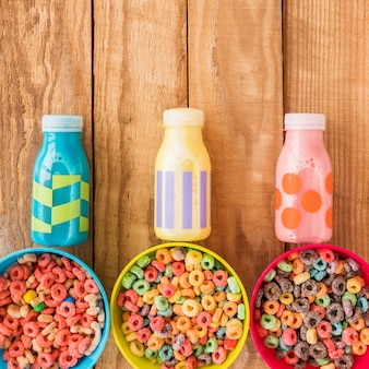 Bowls of cereals with bottles on table