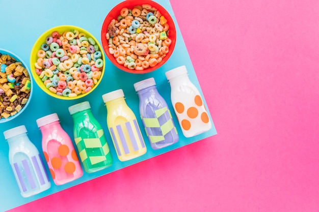Bowls of cereals with bright milk bottles