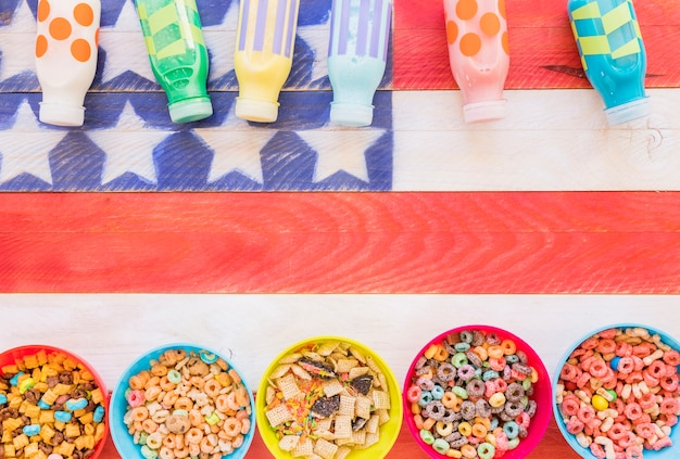 Bowls of cereals with milk bottles on table