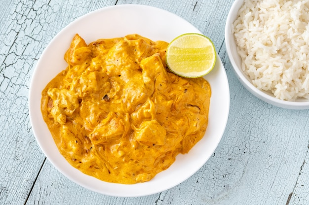 Bowls of chicken curry and cooked white rice