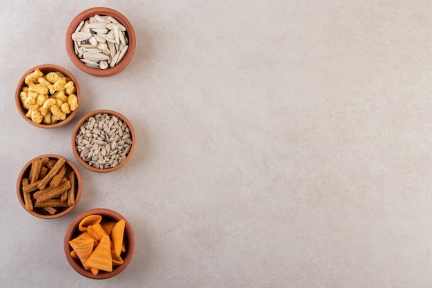Bowls of chips, crackers and sunflower seeds on stone surface.
