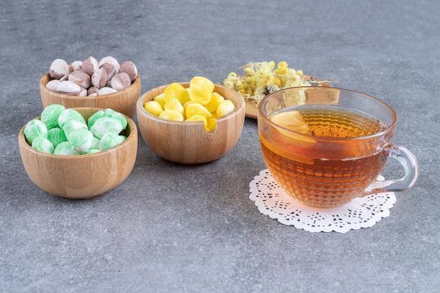 Ciotole di caramelle colorate con tè caldo su superficie di marmo