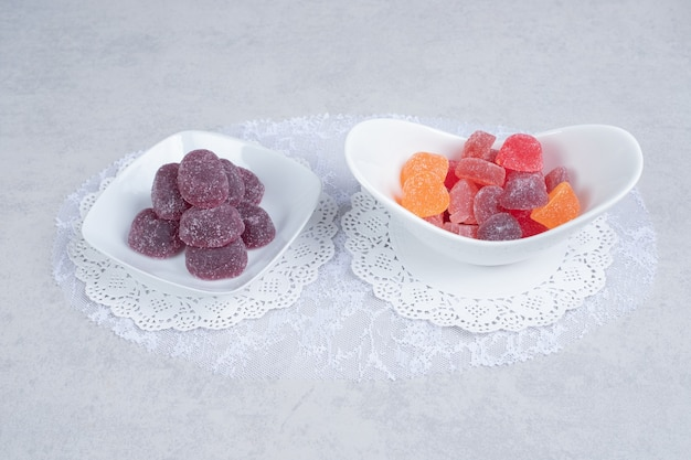 Bowls of colorful marmalades on white table. high quality photo