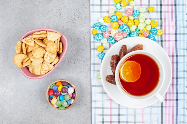 Bowls of cookie chips and candy with dates and scattered candy on marble surface.
