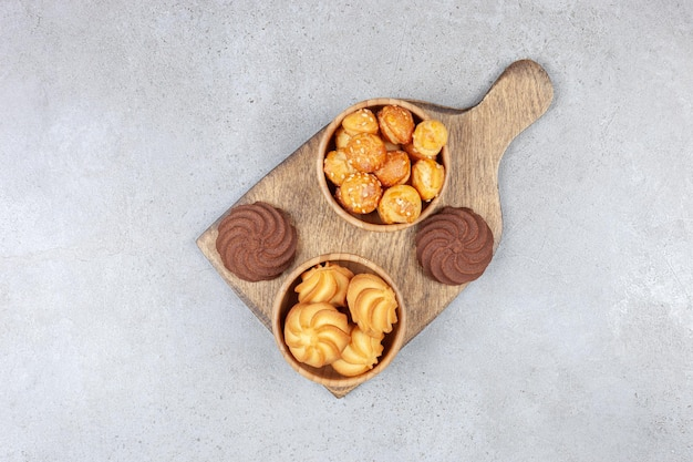 Bowls of cookies next to brown cookies on wooden board on marble surface.