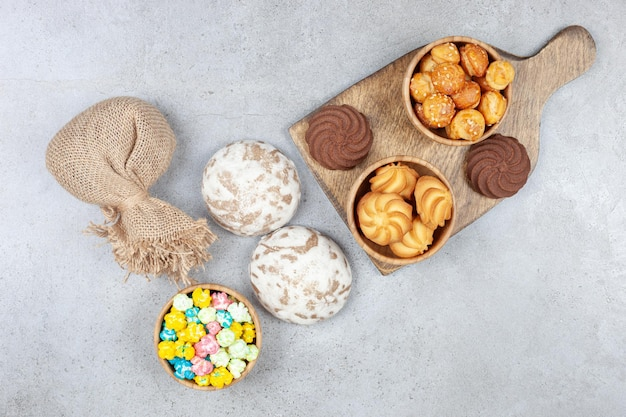 Bowls of cookies next to brown cookies on wooden board with russian sweets, a sack and a bowl of candy on marble surface.