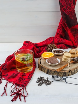 Bowls of cookies and cloves,citrus fruits on a wooden board with herbal tea,red scarf and a tea strainer