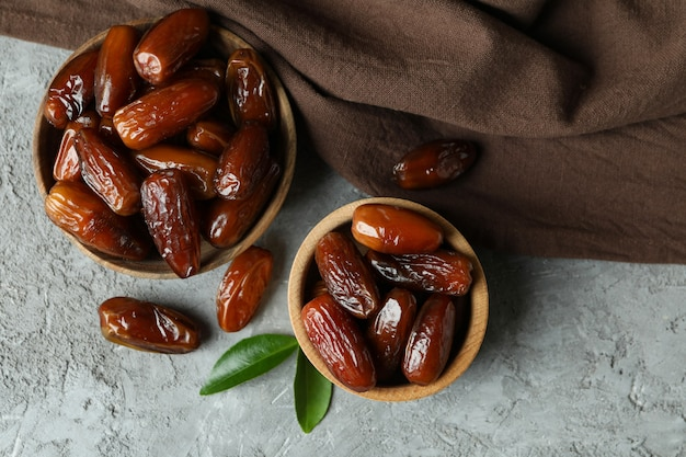Bowls of dried dates and kitchen napkin on gray textured background