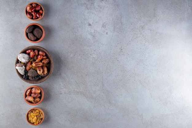 Bowls of dried organic dates, persimmons and raisins on stone background.