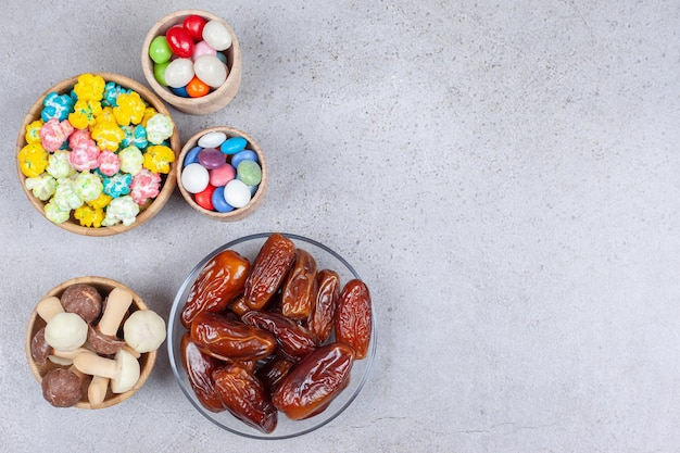 Bowls filled with dates, chocolate mushrooms and colorful candies on marble surface