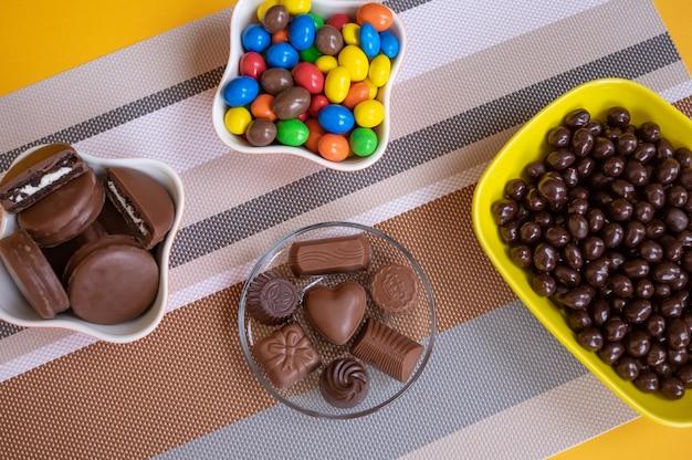 さまざまな色や形のさまざまな種類の茶色とカラフルなチョコレートで満たされたボウル