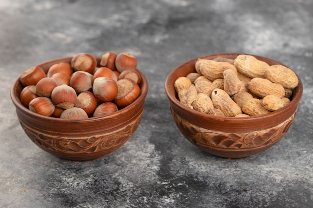 Bowls full of healthy peanuts and hazelnuts in shell placed on a stone table .