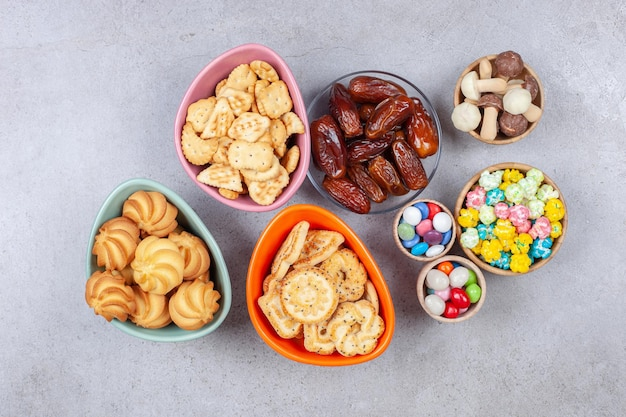 Миски, полные конфет, печенья, крекеров, фиников и шоколадных грибов на мраморном фоне. фото высокого качества