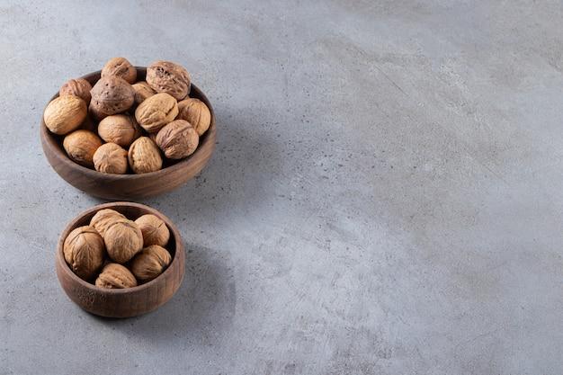 石のテーブルの上に置かれたシェルの健康的なクルミでいっぱいのボウル。