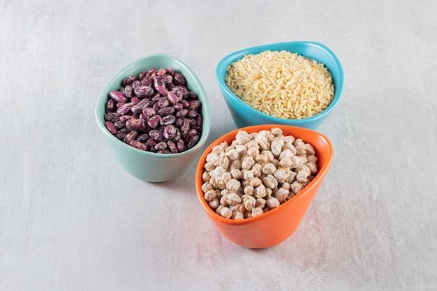 石のテーブルに置かれた未調理のさまざまな種類の豆でいっぱいのボウル。