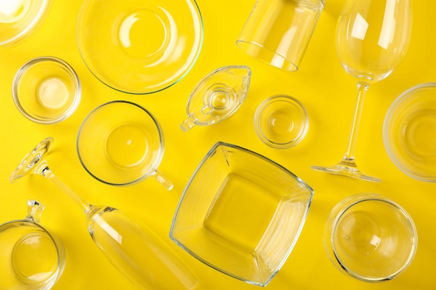 Bowls, glasses and cups on yellow background, top view