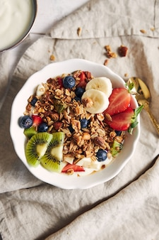 Bowls of granola with yogurt, fruits and berries on a white surface