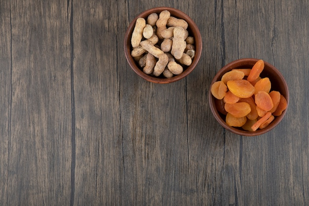 Bowls of healthy dried apricot fruits and peanuts in shell on a wooden table .