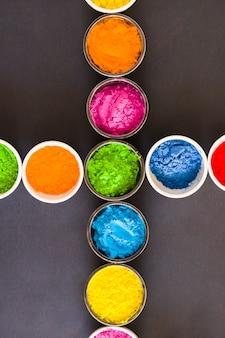 Bowls of holi color powder arranged on gray backdrop