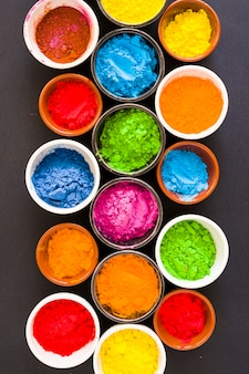 Bowls of holi color powder on black background