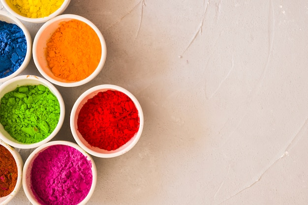 Bowls of holi color powder on concrete background
