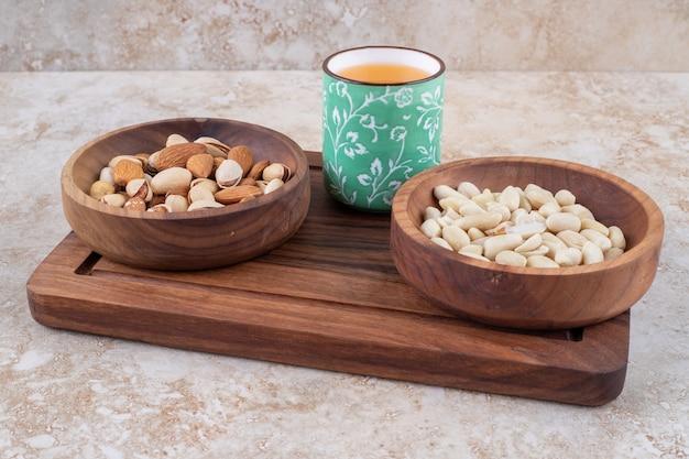 Ciotole di noci e una tazza di succo su una tavola