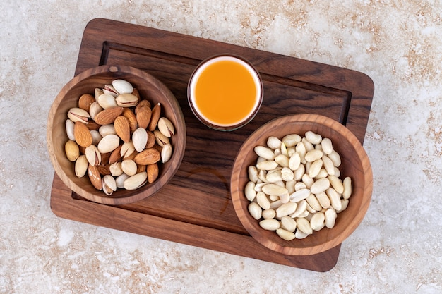 Bowls of nuts and a cup of juice on a board