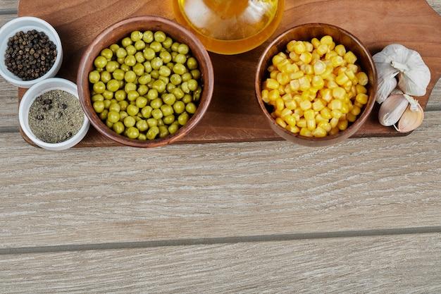 木の板に茹でたスイートコーンとグリーンピース、スパイス、油、野菜のボウル。