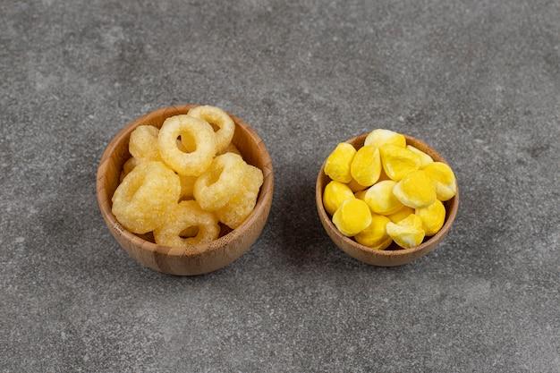 Миски конфет и конфет на мраморе.