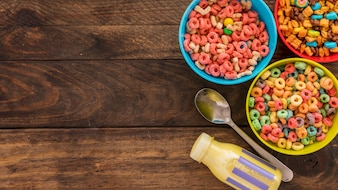 Bowls of cereals with milk bottle and spoon