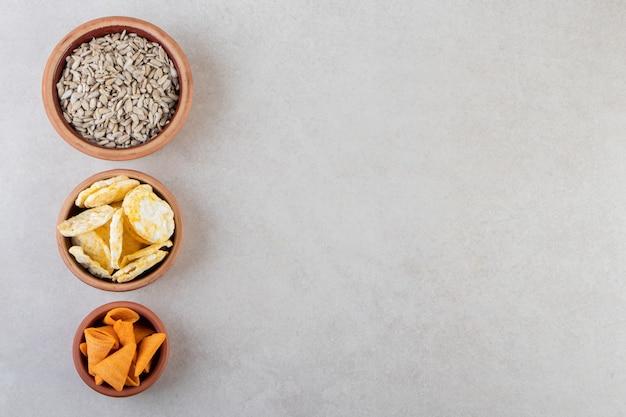 Чаши чипсов, крекеров и семян подсолнечника на каменной поверхности.