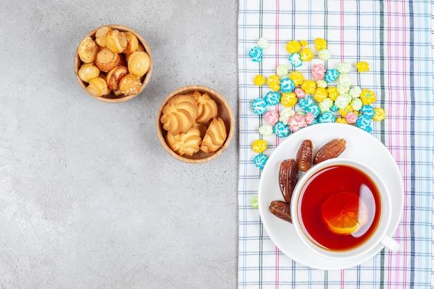 대리석 배경에 날짜와 사탕 쿠키와 차 그릇. 고품질 사진