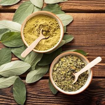 Чаши с измельченными зелеными листьями и порошком для чая