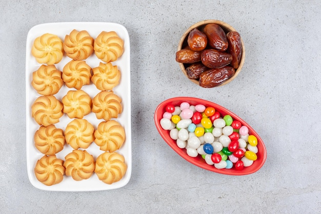 Миски с финиками и конфетами рядом с пачкой хрустящего печенья на тарелке на мраморном фоне. фото высокого качества