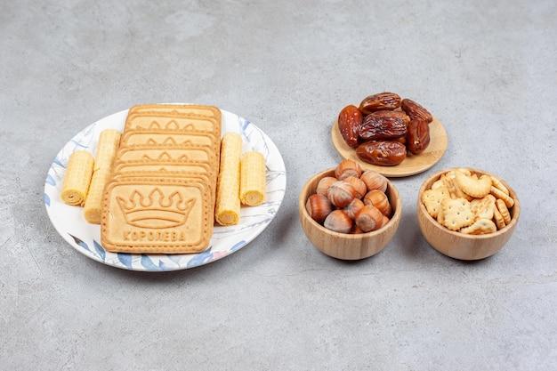 날짜, 헤이즐넛, 크래커의 그릇은 대리석 배경에 접시에 늘어선 비스킷 옆에 있습니다. 고품질 사진