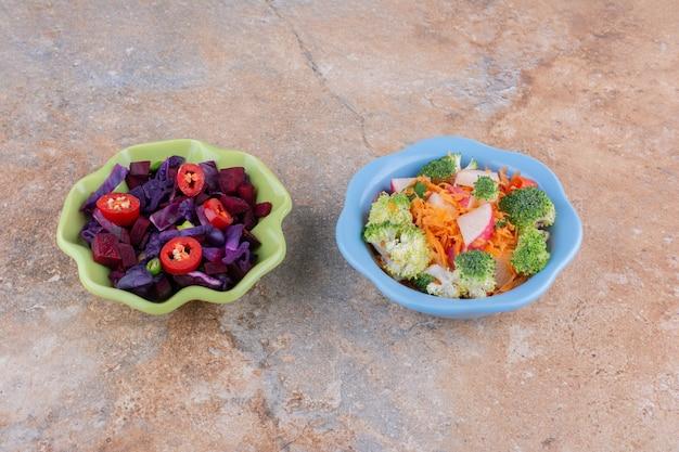 Чаши разных салатов на мраморной поверхности