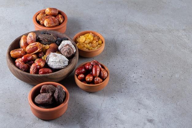 Чаши сушеных органических фиников, хурмы и изюма на каменной поверхности