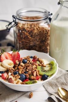 흰색 표면에 요구르트, 과일, 딸기와 그 라 놀라 그릇